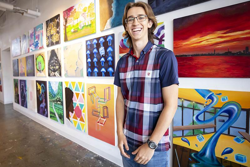 First-year student, Ezra Feder, standing in front of paintings and smiling.