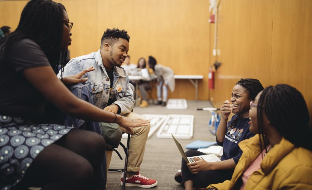 A group of students exchange smiles during a break in choral practice