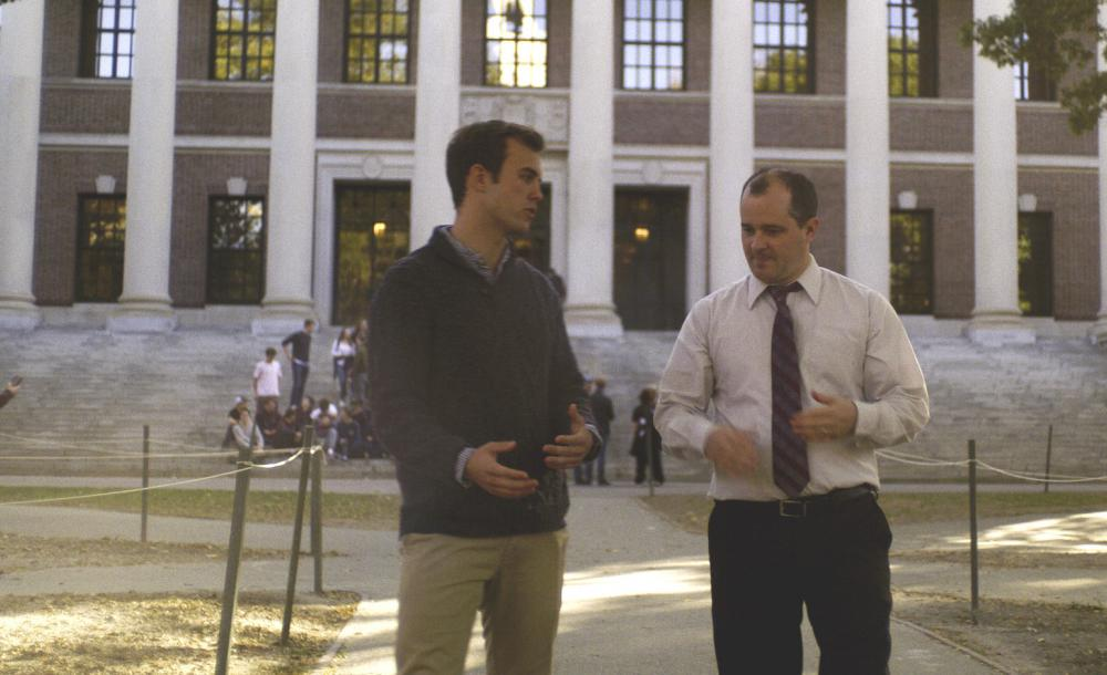 A student and a faculty walk and talk through Harvard Yard.
