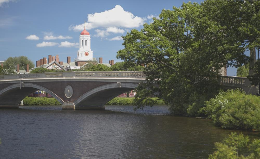 View of a bridge over the Charles river. Harvard campus can be seen in the background.