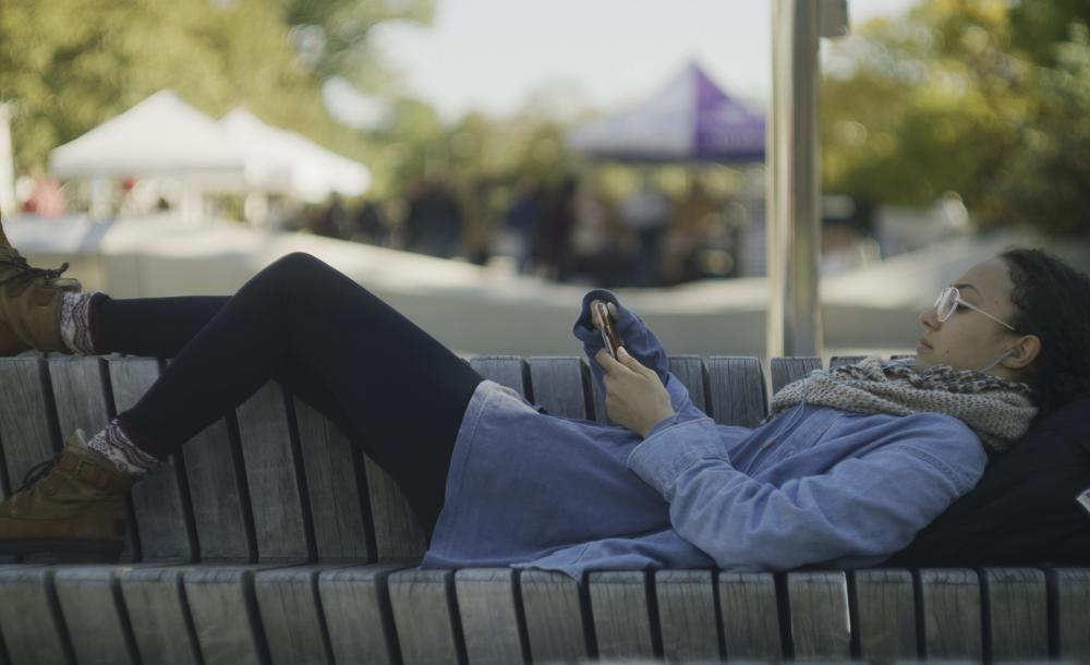 Student laying on bench at Science Center Plaza with her phone