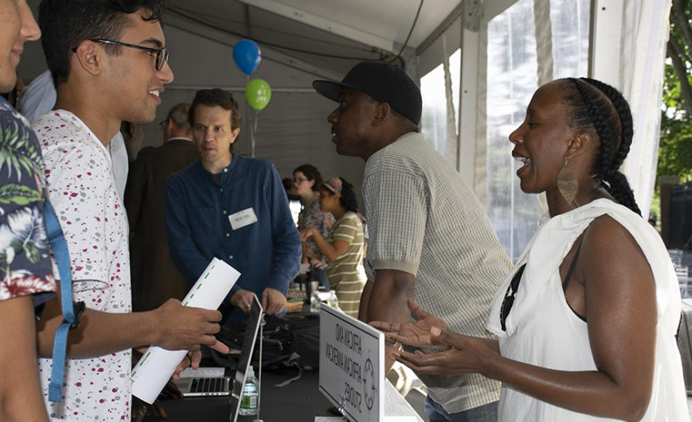 student and adviser talking at a table during the fair