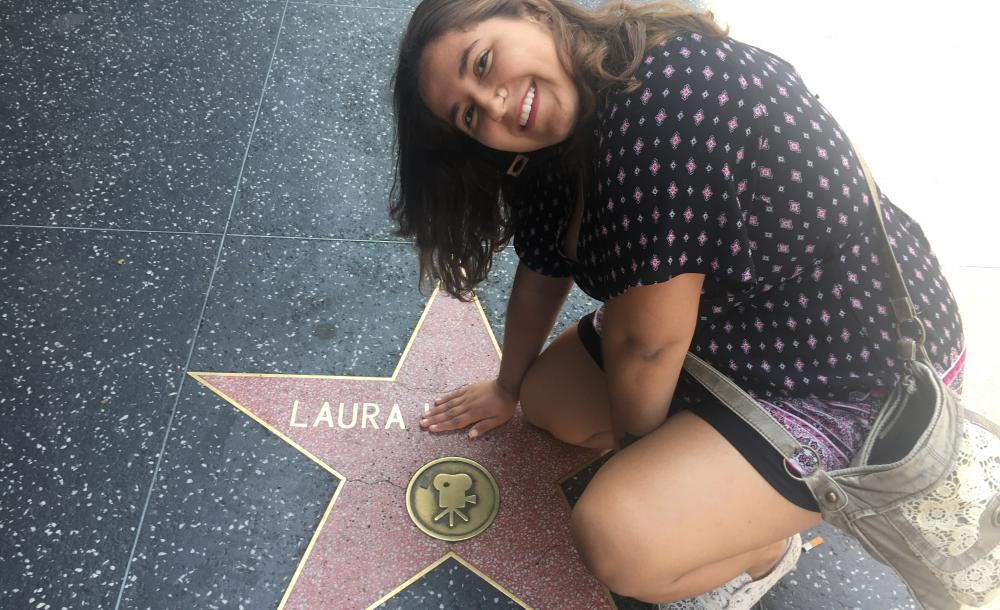 student sitting on the Hollywood Walk of Fame
