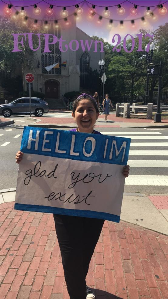 student holding sign that reads: 'Hello I'm glad you exist""