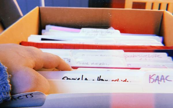 Hand going through files in a box at an archive