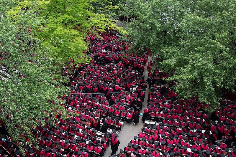 view from above of graduates sitting in Harvard Yard during commencement