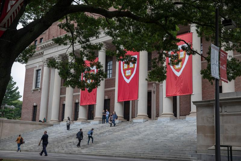 Crimson Harvard banners hanging from Widener Library