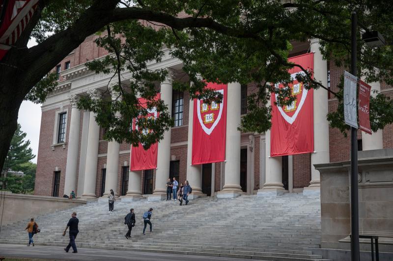 Crimson Harvard banners hanging from Widener Library