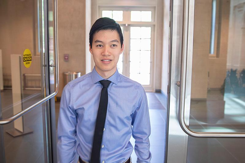 Michael Chen '20 standing in a doorway smiling at he camera.