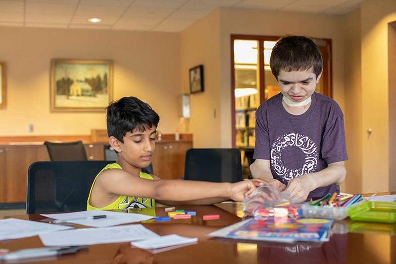 Ben Elwy '23 (right) is teaching Arabic and cultural education to children at the Wellesley Free Library.