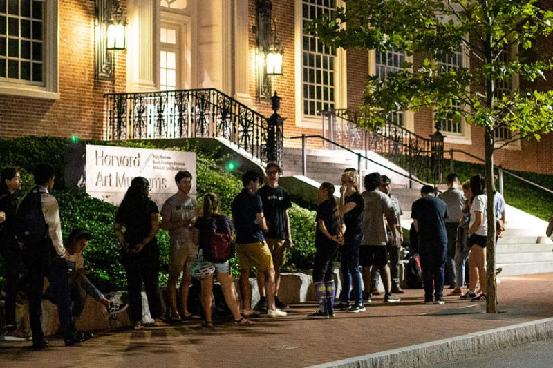 students standing outside at night waiting to get into the Art Museum