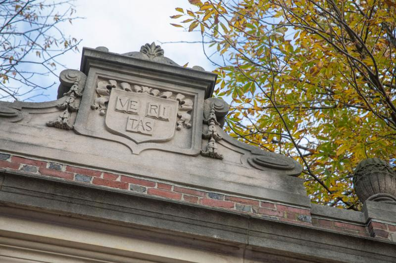 The Veritas shield engraved on one of the gates around Harvard Yard