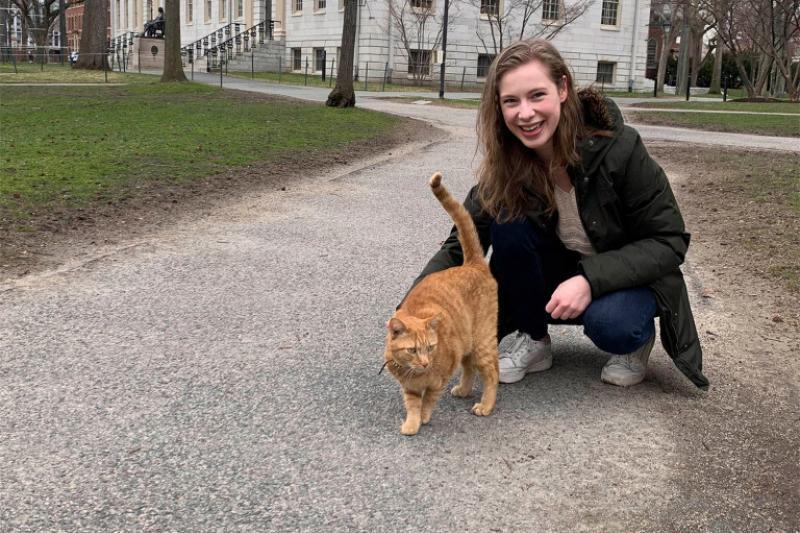 Barbara Oedayrajsingh Varma walks through Harvard Yard with Remy the cat.