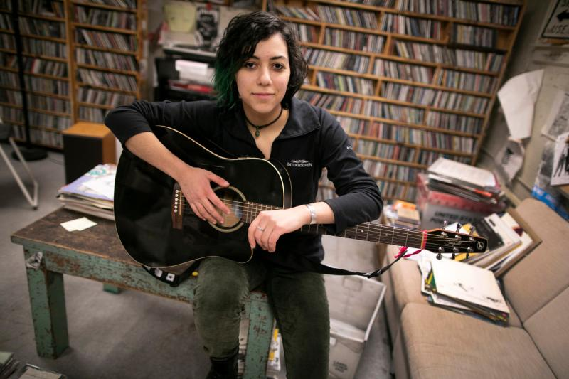 Emily Spector '21 is pictured with her guitar at WHRB, the radio station at Harvard, where Spector is the general manager.