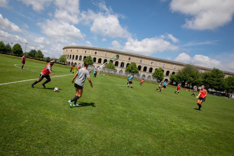 Members of the Harvard community playing soccer outside of Harvard Stadium.