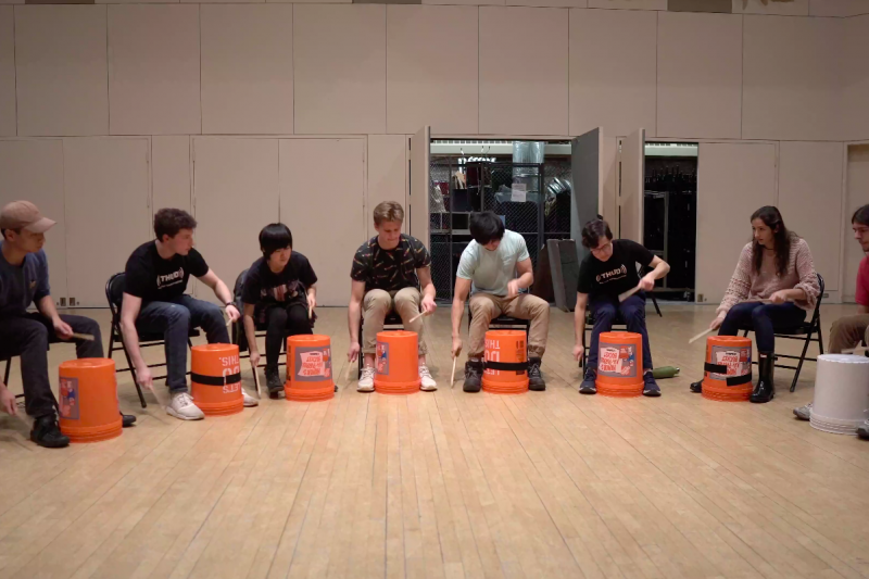 The Harvard Undergraduate Drummers perform a musical number using buckets.