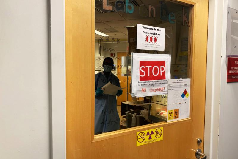 Research associate Aditya Paul works in the Duraisingh Lab, where signs illustrate new safety protocols.