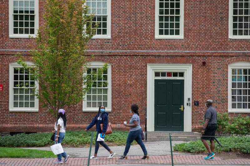 Lara Dada '24 (second from left) walks with her family past Massachusetts Hall.