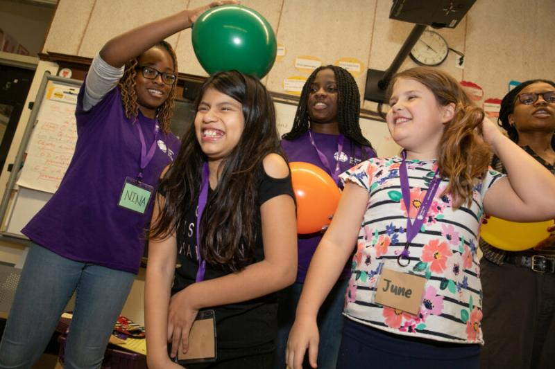 Back in early March, Nina Uzoigwe '21 (left) demonstrated static electricity with a balloon on the head of a student as Kaelyn Brown '21 (back left) and her sister Cierra Brown '23 (back right) looked on. The pandemic forced the club to halt its in-person programming, moving it online.