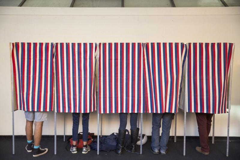 Five individuals vote in the booths at the polls.