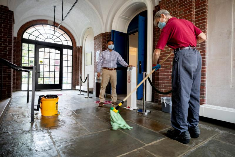 "Harvard custodial manager Elson Callejas (left), who led the distribution of ""cleaning kits"" to 1,200 students moving onto campus, is shown in Lowell House with worker James Normile."