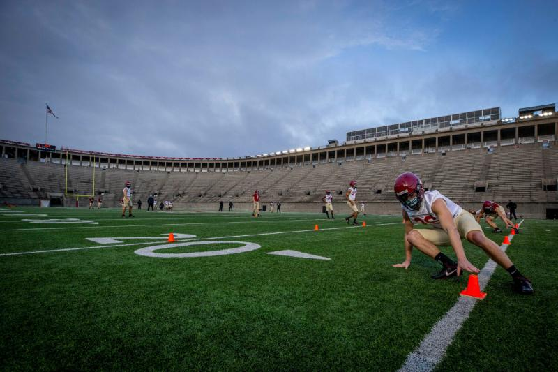 Defensive back Garrett Sharp '24 does an end-of-practice drill with his teammates at sunup in Harvard Stadium.