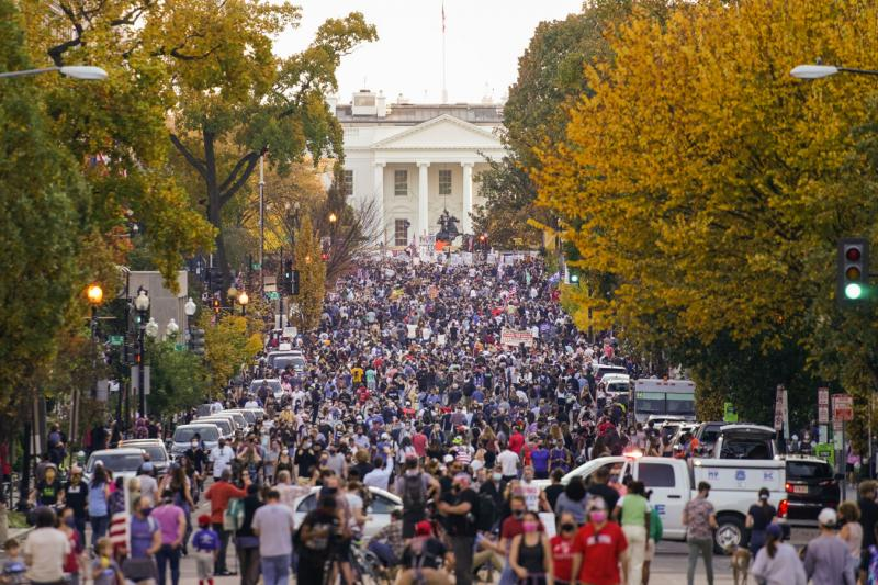 A crowd gathers along 16th Street in front of the White House on Saturday to celebrate the presidential race being called in favor of President-elect Joe Biden.