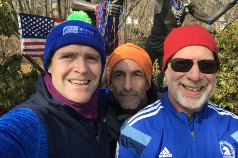 Taking a break during a Sunday run last February, Bob Manson, M.P.A. '04, (left) poses with Daniel Lieberman '86 (right) and a fellow runner in Newton at Heartbreak Hill, along the Boston Marathon course.