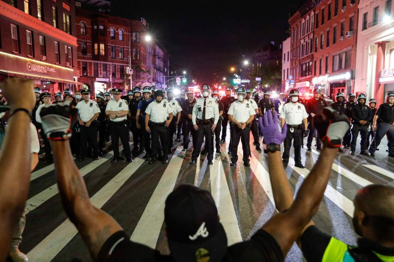 Protesters take a knee in front of New York City police officers during a solidarity rally for George Floyd, June 4, 2020.