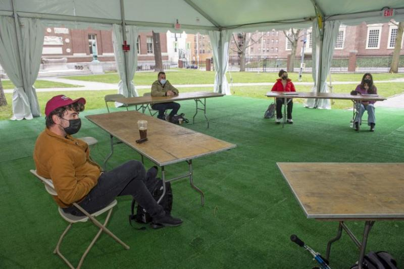 Juan Espinoza, a third-year Harvard Law School student, joins others in a tent in the Yard for English with instructor Sam Marks.