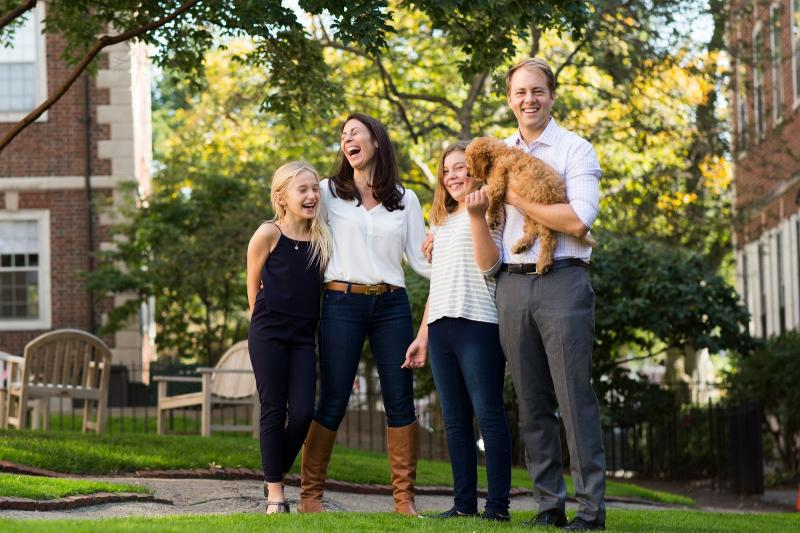 A portrait of Janine Santimauro and David Deming, faculty deans of Kirkland House, with their two daughters and dog.