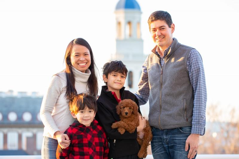 A portrait of Leslie Duhaylongsod and Eric Beerbohm, faculty deans of Quincy House, with their two sons and dog.