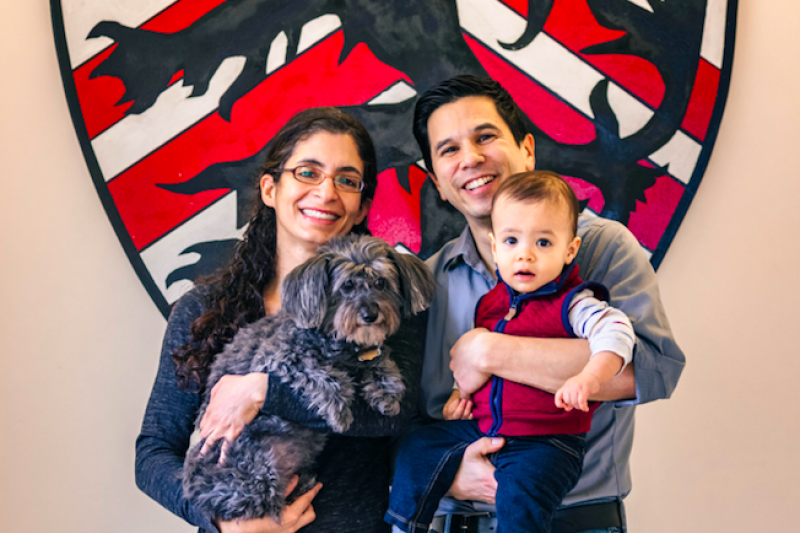 A portrait of Kiran Gajwani and Stephen Chong, faculty deans of Winthrop House, with their son and dog.