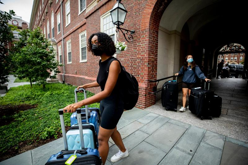 Halima Badri '23 (left) and Maria Gonzalez '23 enter the Lowell House courtyard with their luggage.
