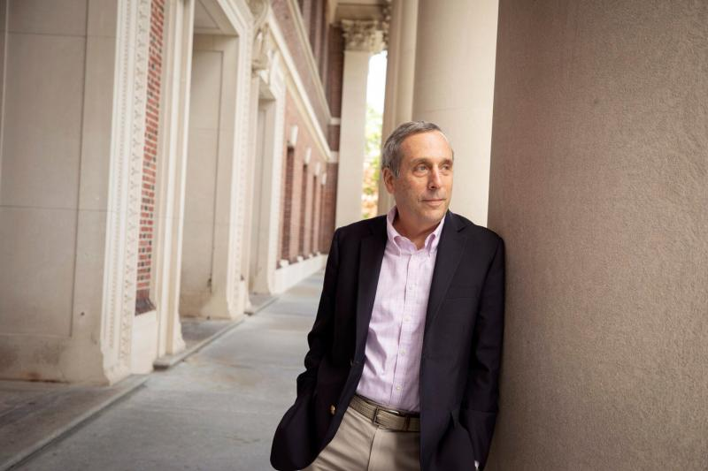 Larry Bacow poses against column at Widener Library