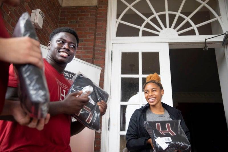 """Football player Kwaku Adubofour '24 and DaLoria Boone '22 of women's track and field receive their """"Major H"""" varsity letter sweaters at the first distribution day since 2019."""