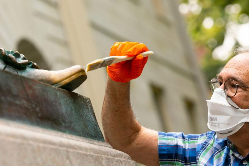 John Harvard's statue's foot being brushed during the renovation process