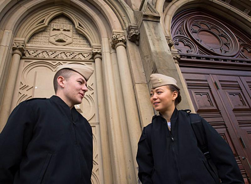 Two students in dark jackets and tan hats stand in front of a Harvard Chapel door