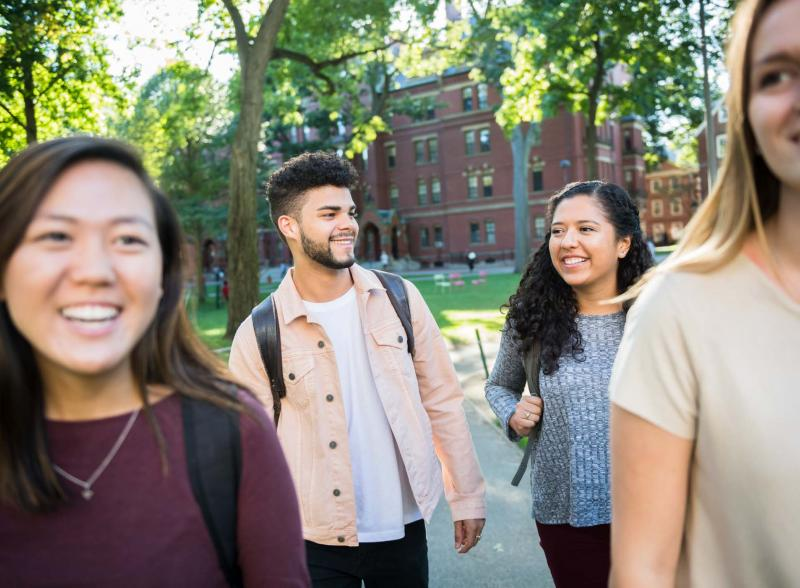 Four students smiling and walking through campus