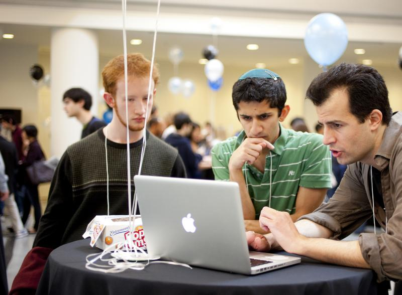 3 students in front of a laptop at a tech fair