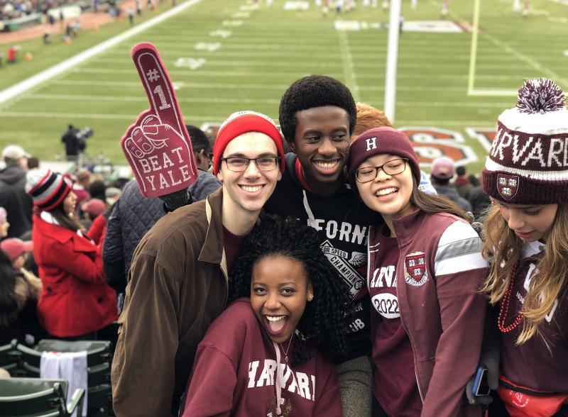 Four students cheering in the stands at a Harvard football game
