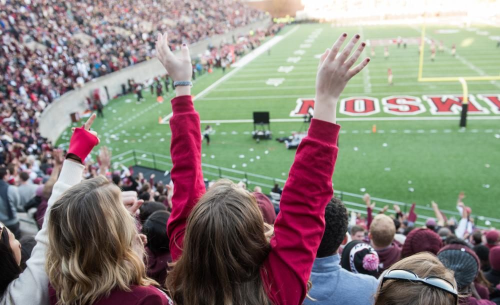 Students cheering at a Harvard football game