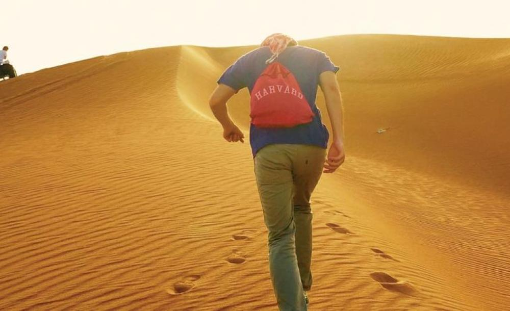 Student with Harvard backpack in desert