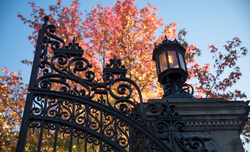 Close up of gates of Harvard Yard with fall foliage behind them