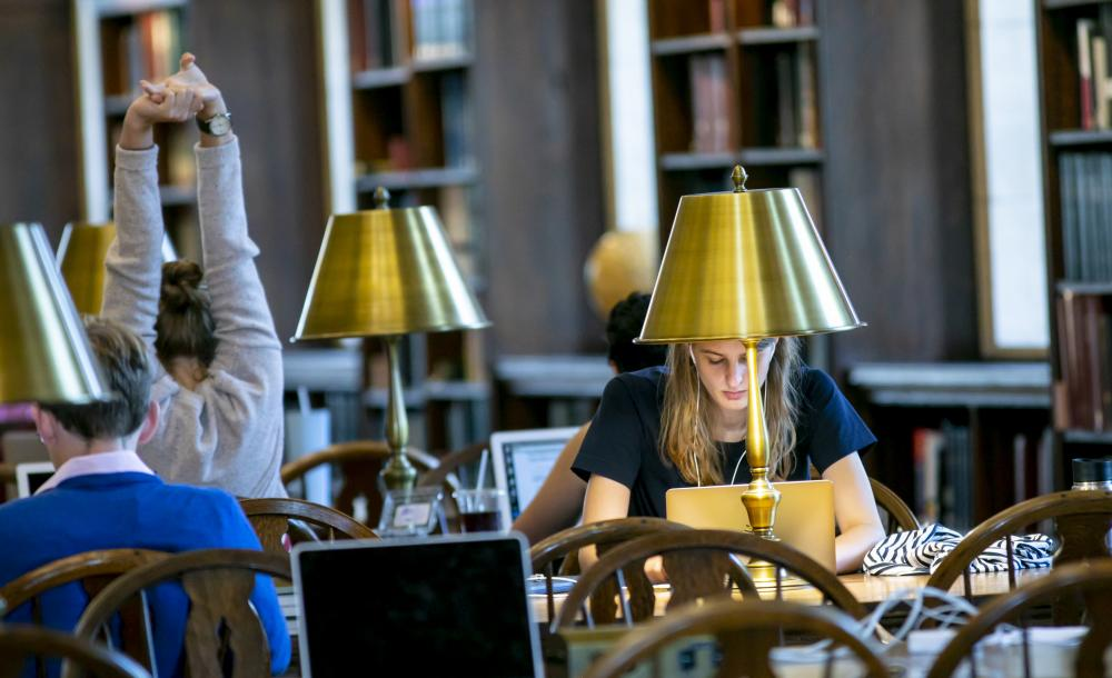 students sitting at a table studying in the library