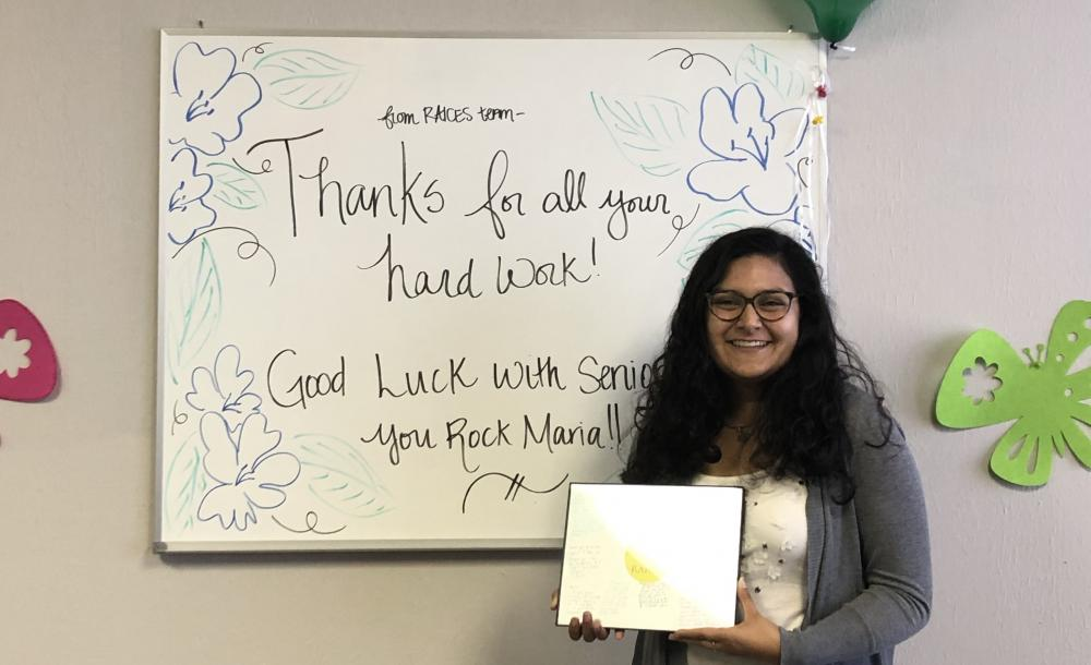 Maria posing in front of a farewell message at the end of her internship.