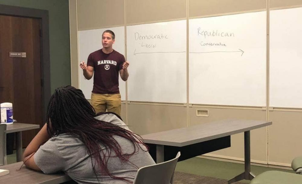 Student lecturing in front of a white board