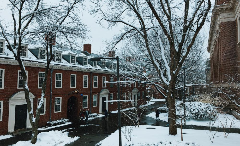 Snow falling outside brick dorm building