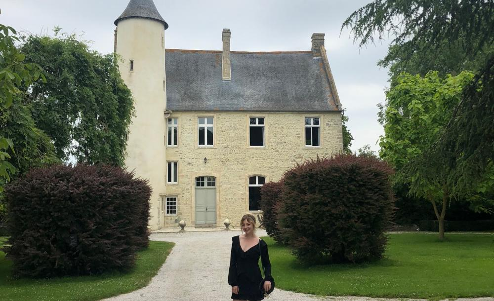 Malia at Chateau Monfreville, a castle in northern France, with greenery and sky in background