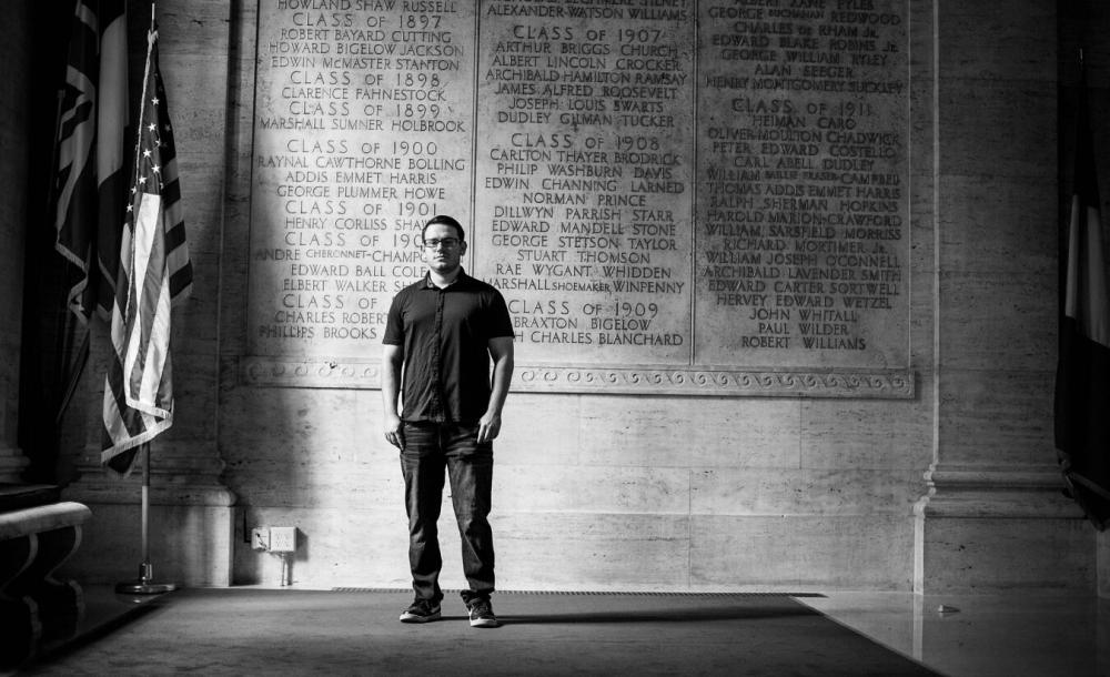 James stands in front of a wall etched with names of Harvard veterans